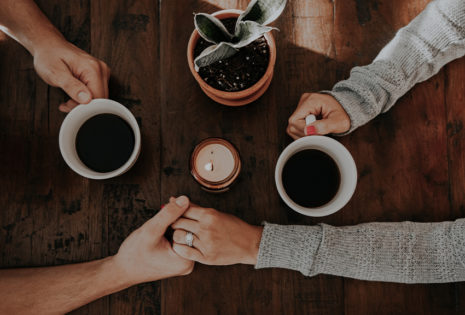 two holding hands and drinking coffee