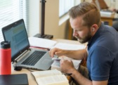 man studying with laptop and bible