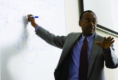Black Denver faculty member standing at whiteboard
