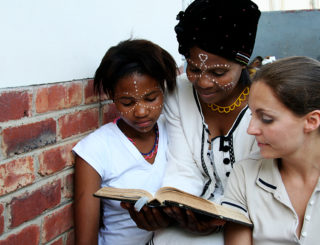 2 women and a child reading a bible