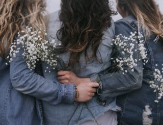 group of three girls holding flowers with arms around each other