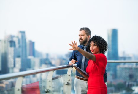 man and woman standing on city balcony