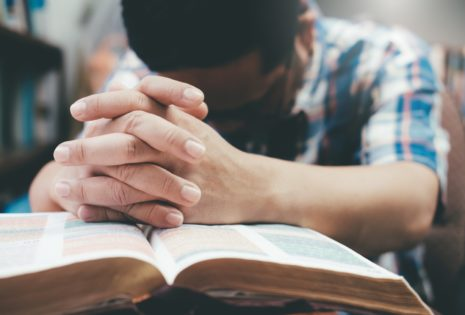 man praying with hands together on bible