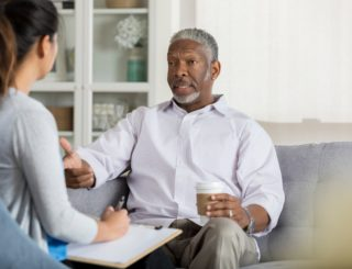 man sitting on couch and talking to woman
