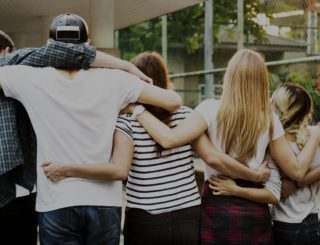 group of people with arms around each other smiling