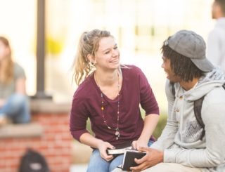 male and female student smile and talk