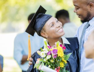 graduate smiles at husband after ceremony