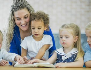 children and a woman smiling and looking at bible