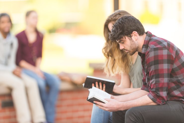 man and woman sitting and looking at bibles
