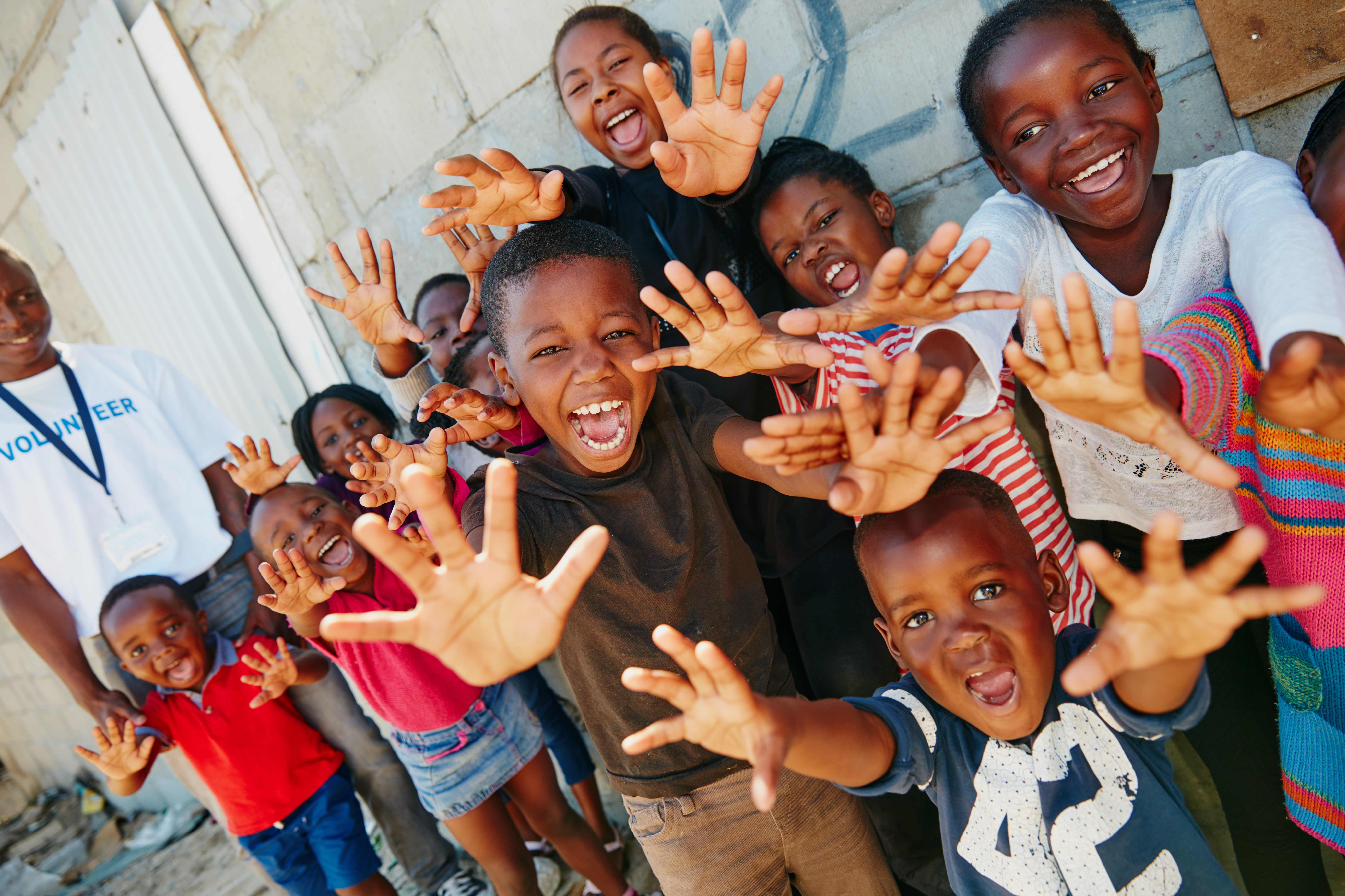 group of children holding out hands and smiling