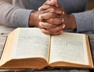 hands together on top of bible