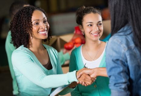 women shaking hands and smiling
