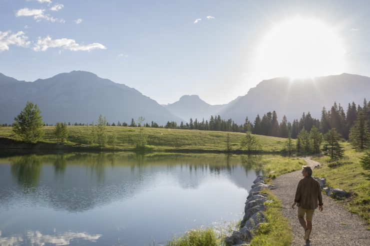 Man walks along pathway beside a lake towards the rising sun