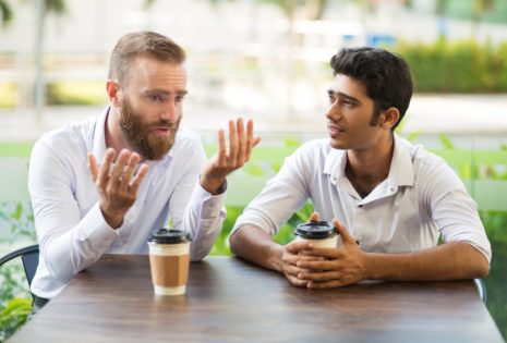 two men talking at table outside