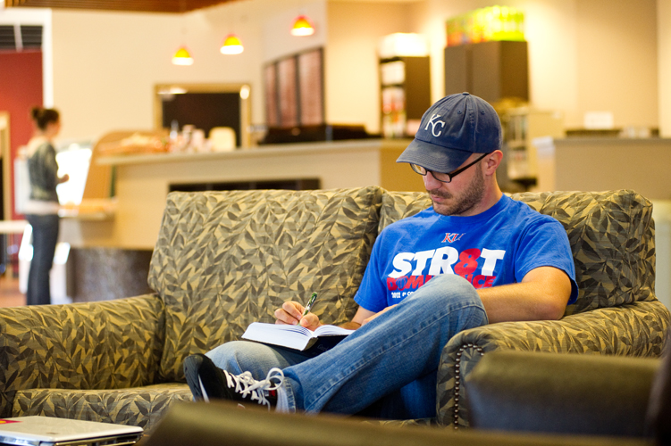 man sitting on couch and writing in book