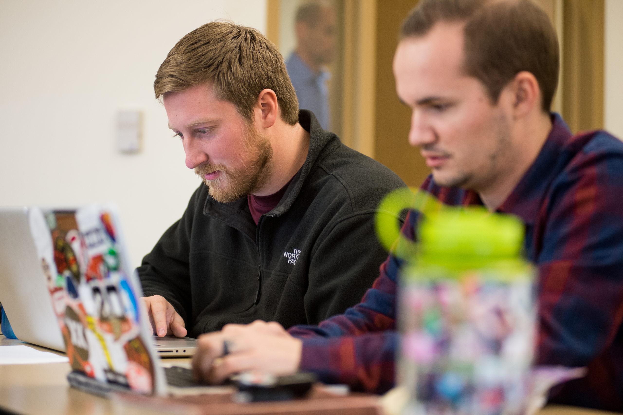 two men on laptops