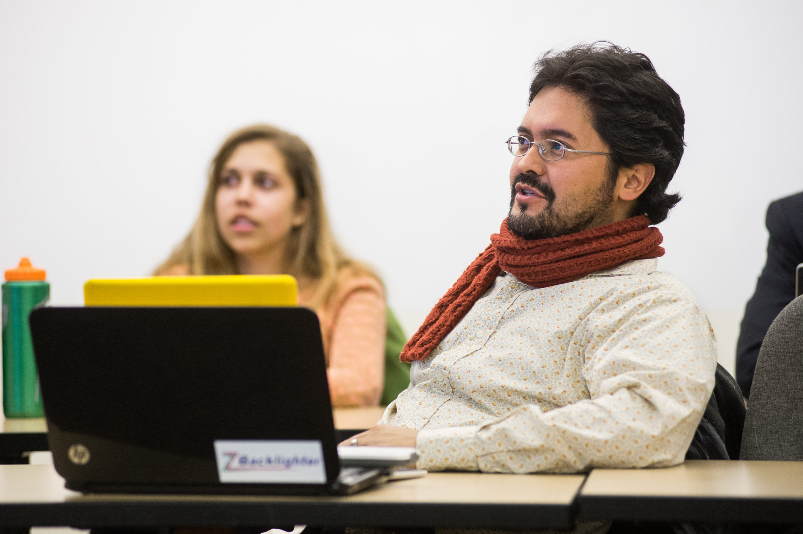 man talking in class sitting in front of laptop