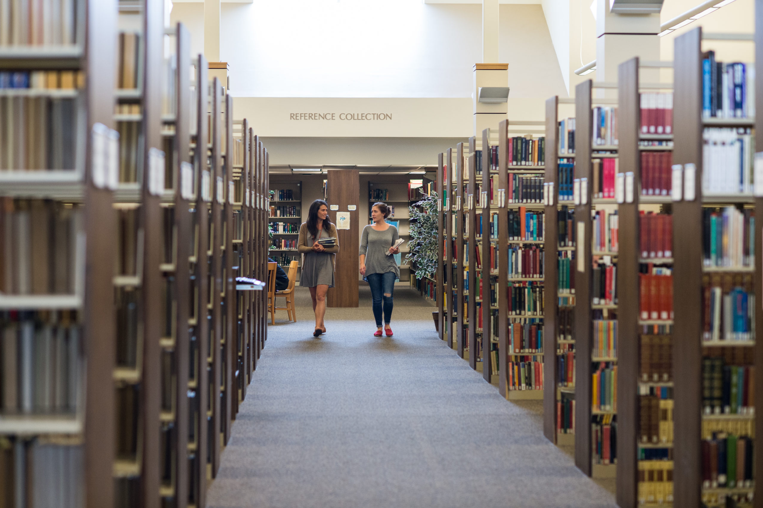 two women walking and talking in library