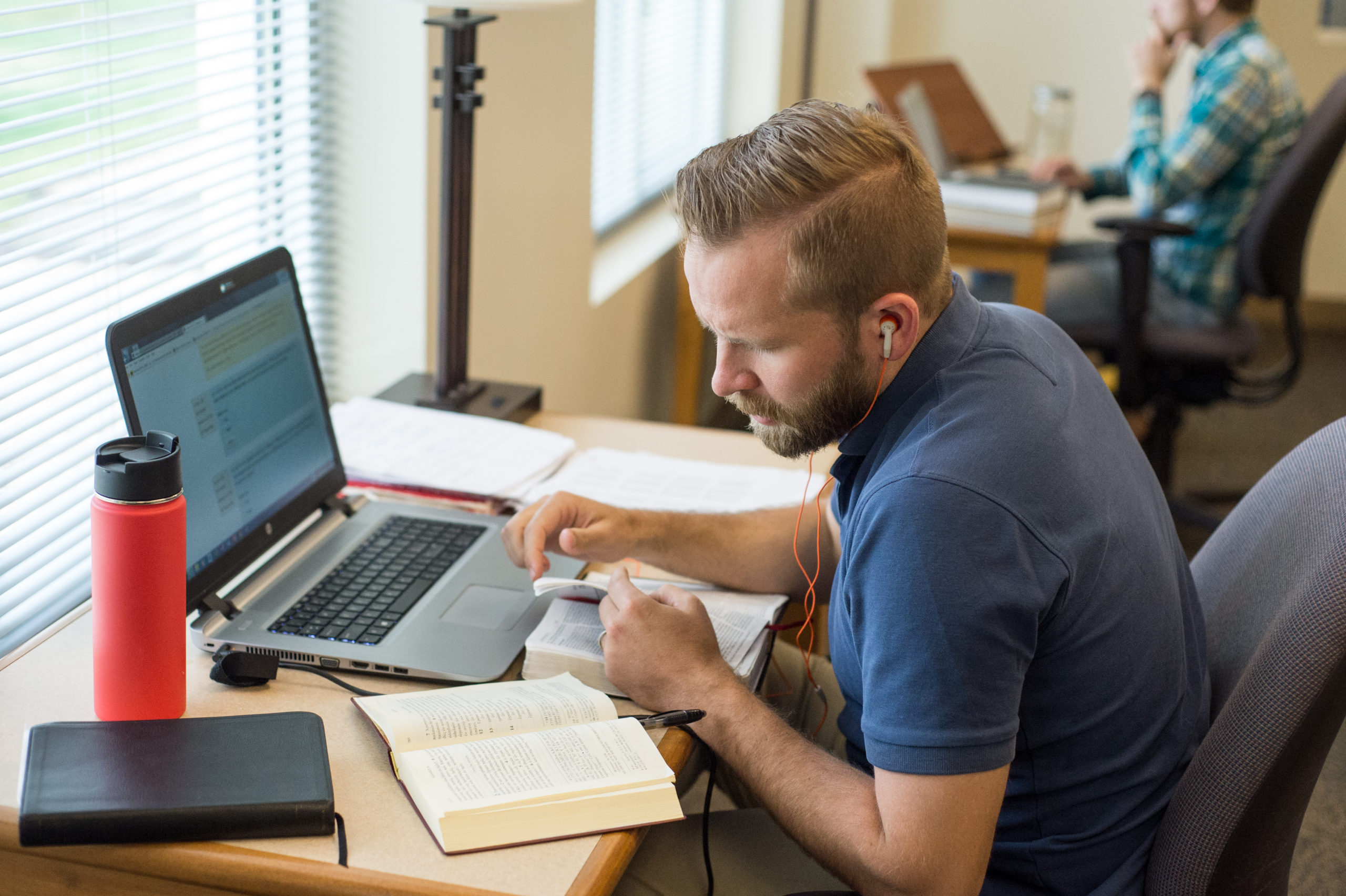 man with headphones in studying bible