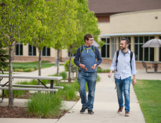 two men walking and talking on campus