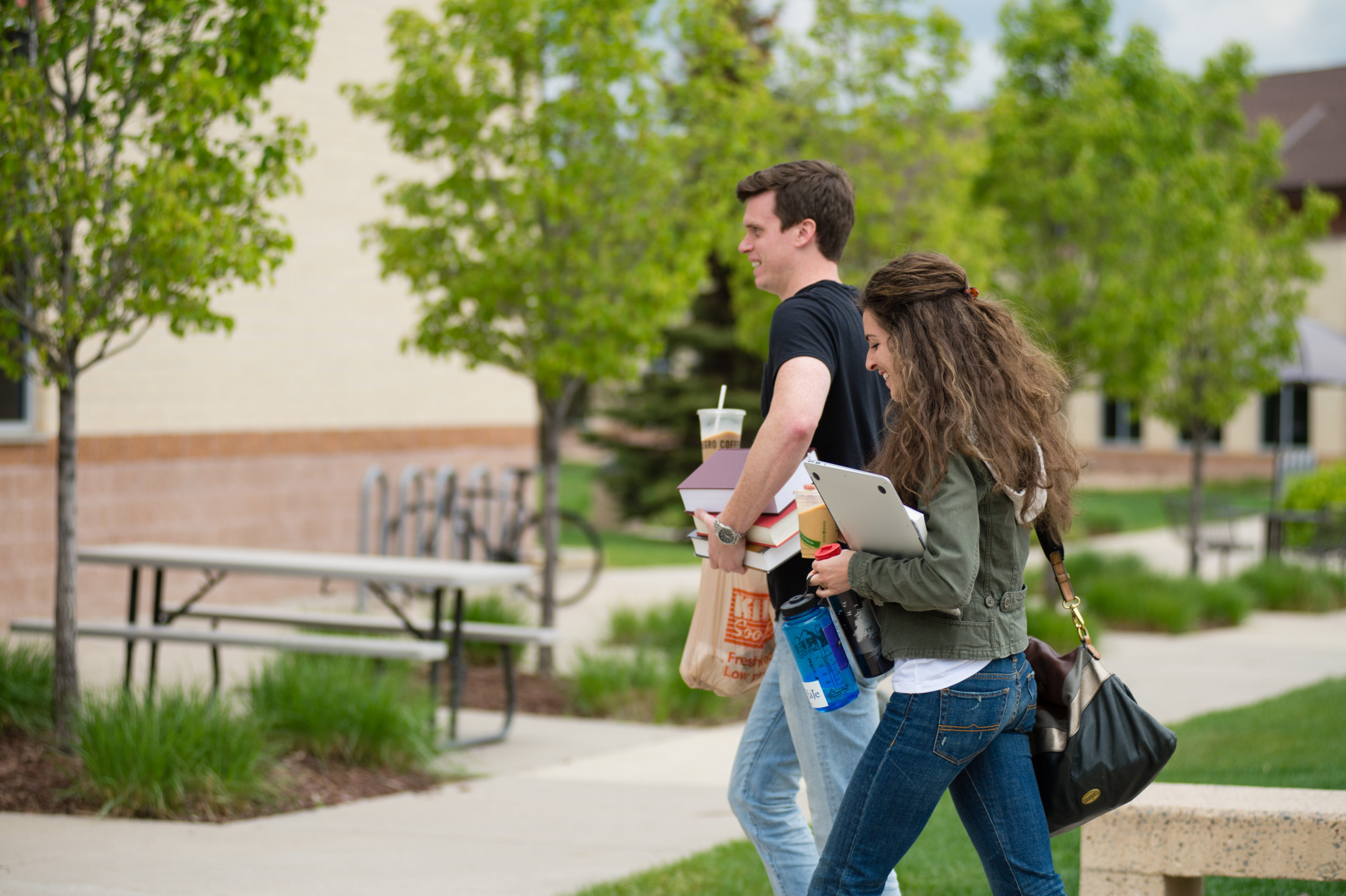 man and woman walking and talking on campus