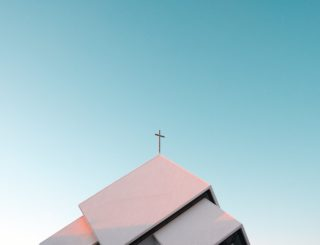 cross on building with sky background