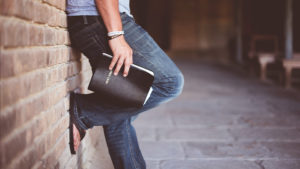 person holding bible waist down view