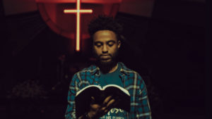 male student looking at bible with glowing cross