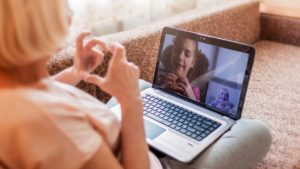 internet video conference with child and woman making hearts