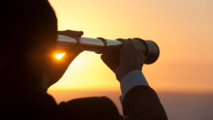 person looking into sky with telescope