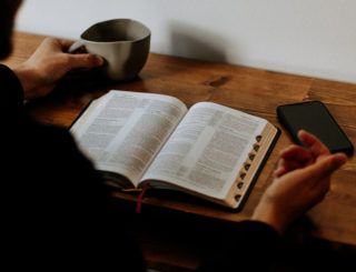 person with coffee cup phone and bible on table