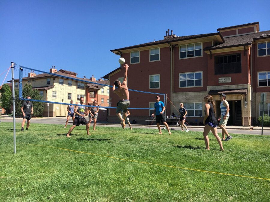 people playing volleyball outside of campus apartments