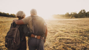 Older couple pictured from the back with arms around each other