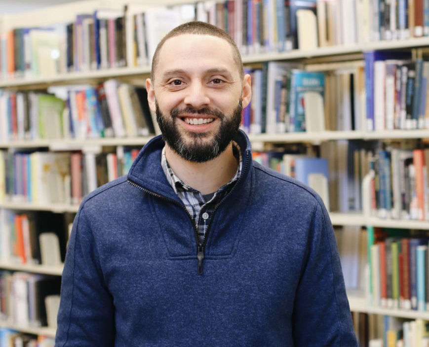 Smiling male Denver Seminary student with beard looking directly at camera