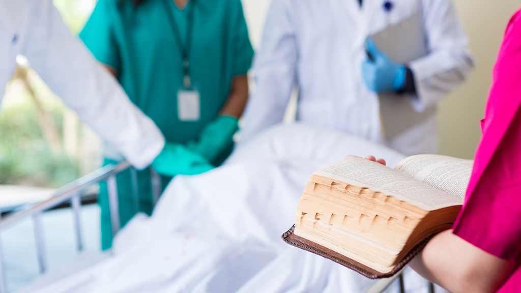 A Bible open in the hands of a healthcare worker standing by a bedside