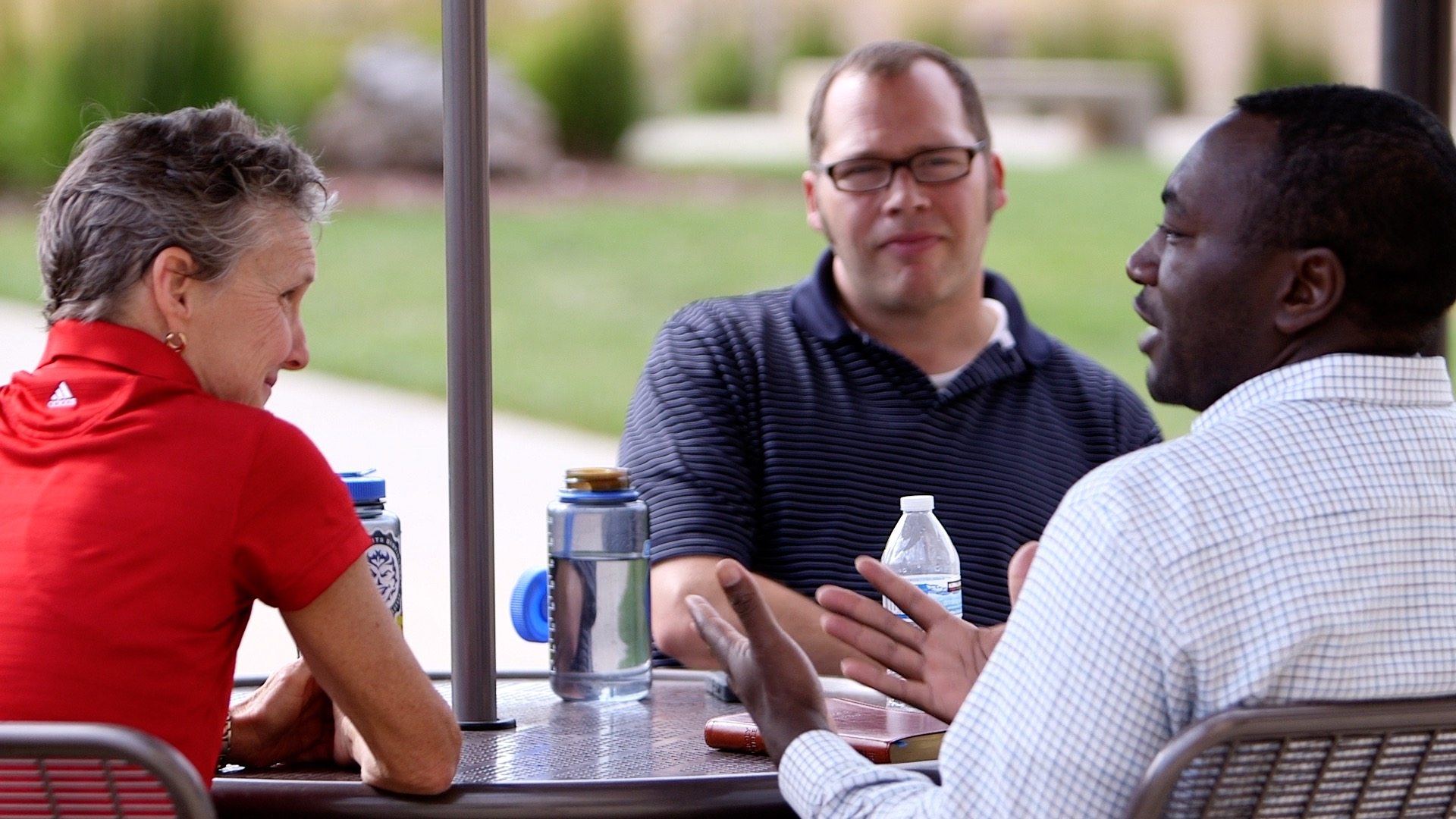 Three Denver seminary faculty members sitting at a table outside