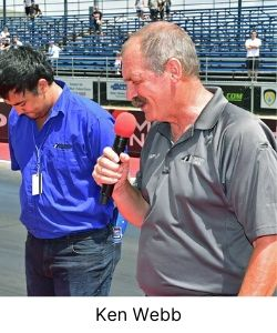 Man praying at a speedway before a car race with microphone in hand