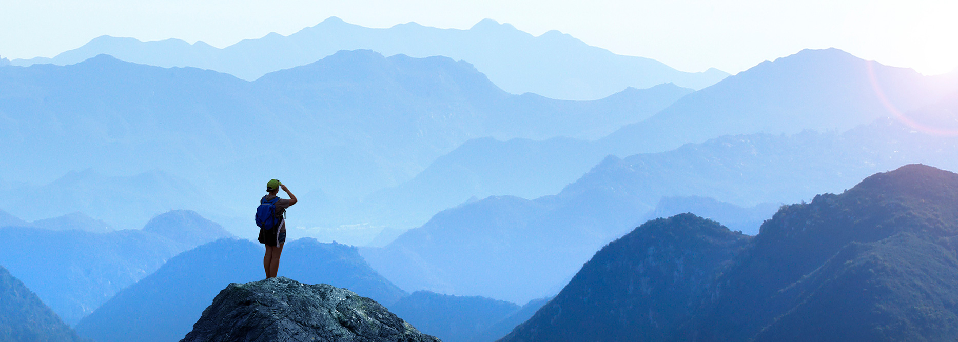 Person standing on a hill looking across a mountain range