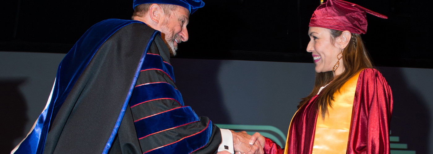 Seminary president shakes hand with graduate at commencement